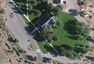 Aerial view of the church with the parking area, green grass and elk.